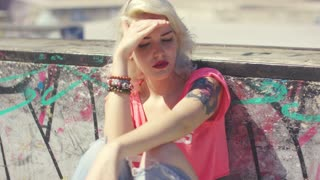 Trendy young woman with a tattoo on her arm sitting in the hot summer sunshine shielding her hands with her hand watching and waiting