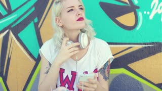 Trendy young woman with tattoos on her arms sitting in front of a colorful graffiti covered wall listening to music on headphones using her mobile
