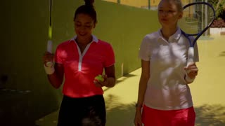 Two beautiful young woman tennis players chatting