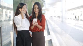 Two businesswomen checking a phone message