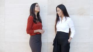 Two chic young women standing chatting