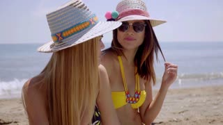 Two female friends on a beach in the summer