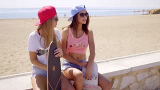 Two good looking female skating friends with caps
