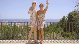 Two happy elegant young women standing waving