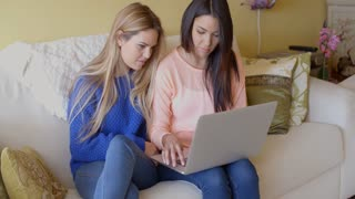 Two happy young women browsing the internet