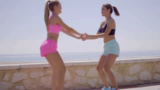 Two happy young women exercising together