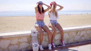 Two laughing friends in shorts sitting near beach
