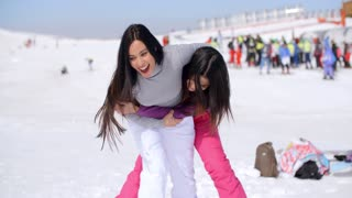 Two playful woman frolicking in the snow