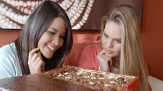 Two pretty women eating chocolates