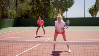 Two pretty women playing a game of tennis doubles