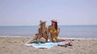 Two sexy young women sunbathing on a beach