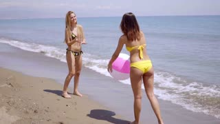 Two women in bikinis playing with a beach ball