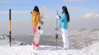 Two women snowboarders enjoying the winter view