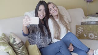 Two young girlfriends taking a selfie at home