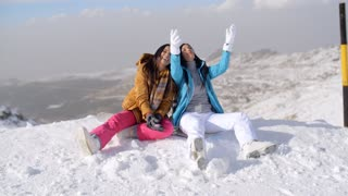 Two young women frolicking in the snow