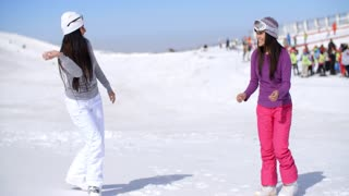 Two young women having a snow fight