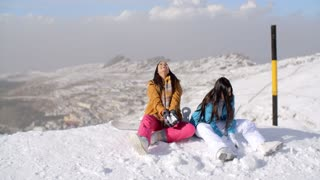 Two young women having fun in winter snow