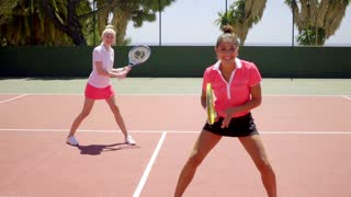 Two young women playing tennis doubles