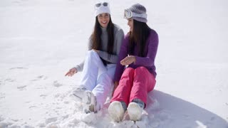 Two young women sitting chatting in the snow