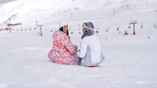 Two young women sitting in snow at a ski resort