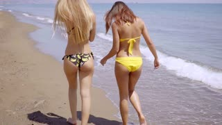 Two young women walking away along a beach