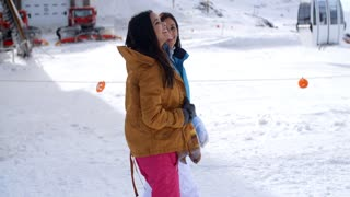 Two young women walking through snow at a resort