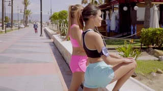 Two young women warming up before exercising