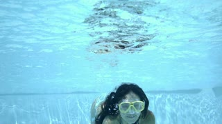 Underwater woman swimming with arms outstretched in bikini and goggles at pool with clear water