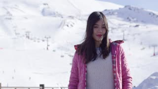 Upper body portrait of smiling young asian woman on snow covered ski resort mountainside. She smiling to the camera.