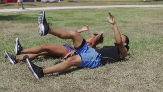 Adult ethnic sporty man and woman lying on green lawn and exercising with legs up in the park in sunny day.