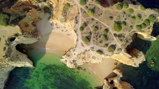 Aerial shot from above of green ocean water washing slightly sandy beach of coastline with rough cliffs in bright sunlight, Algarve, Portugal.