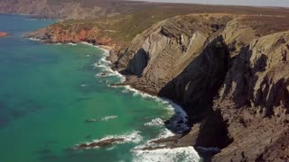 Aerial shot from drone with panoramic view of rocky huge cliffs above calm turquoise water of ocean on tropical coastline of Algarve in Portugal.