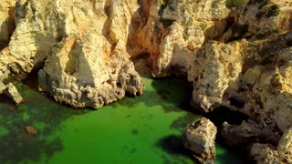 Aerial shot of colorful landscape with white rough cliffs of tropical ocean coastline and green water of calm lagoon, Portugal, Algarve.
