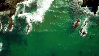 Aerial top view of bay in textured cliffs with green ocean water dashing against rocks in bright sunlight, Algarve, Portugal.
