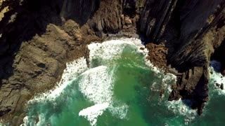 Aerial top view of tide with white foam washing rocky shore of tropical ocean lagoon surrounded with cliffs, Portugal, Algarve.