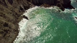 Aerial view from drone of tropical sunlight reflecting in turquoise water of ocean washing rocky shoreline of Algarve, Portugal.