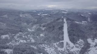 Aerial view of white snow covering spacious valley of mountains range with skiing resort in winter time, Poland.
