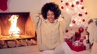 African American Woman with afro haircut sitting by fireplace and white christmas tree covered in red ornaments and having many presents under it