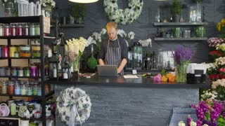 Anonymous man bending over counter while working in floral shop and writing on paper with laptop lying near.