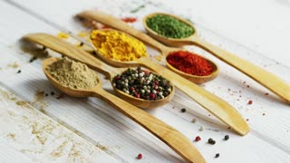 Arrangement of small wooden spoons with assortment of ground spices on wooden table