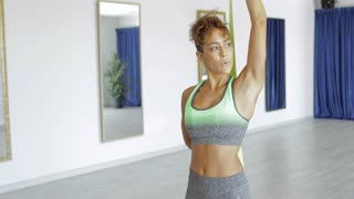 Attractive black woman doing arms stretch exercises and working out hard with eyes closed in dance class.