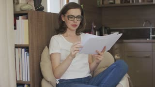 Attractive concentrated female in eyeglasses sitting in comfortable armchair at home and reading papers.