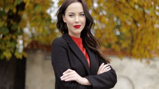 Attractive confident woman with vivid makeup standing in autumn park, keeping her arms crossed and looking at camera.
