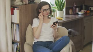 Attractive female in eyeglasses sitting in comfortable armchair at home and using smartphone putting earphones in.