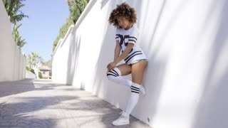 Attractive female wearing sportive knee-high socks and t-shirt posing near white wall touching her hair.
