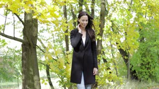 Attractive sad woman in black jacket feeling cold and keeping her arms crossed while walking in autumn park.
