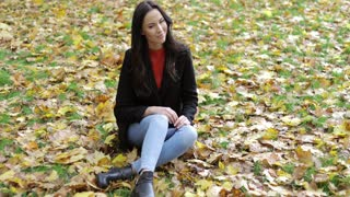 Attractive smiling woman in black jacket sitting on grass covered with yellow leaves and looking at camera during her walk in autumn park.