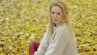 Attractive thoughtful woman in soft beige jumper sitting on ground covered with fallen leaves during her walk in autumn park.