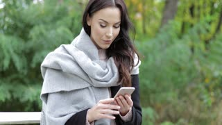 Attractive woman in black jacket and large gray scarf using her smartphone during her walk in autumn park.