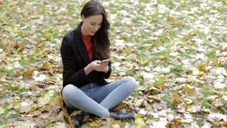 Attractive woman in black jacket sitting on grass covered with leaves and using her smartphone during walk in autumn park.
